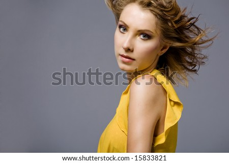 Portrait of attractive young fashion model in yellow dress. - stock photo