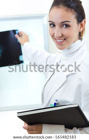 Portrait of attractive young female doctor examining x-ray results - stock photo