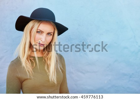 Portrait of attractive young female standing in front of a blue wall and looking at camera. Shot of stylish young caucasian female model with hat. - stock photo