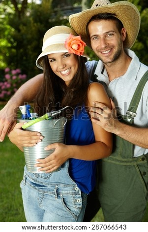 Portrait of attractive young gardening couple embracing, smiling happy. - stock photo