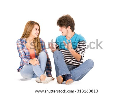 Portrait of attractive young happy couple in love man and woman isolated over white background sitting on floor looking to each other while talking. - stock photo