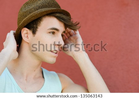Portrait of attractive young man in urban background wearing a sun hat - stock photo