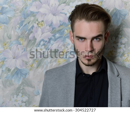 Portrait of attractive young man looking at camera, over floral background. Image toned and noise added. - stock photo