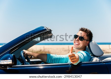 Portrait of attractive young man sitting in blue convertible doing thumbs up. - stock photo