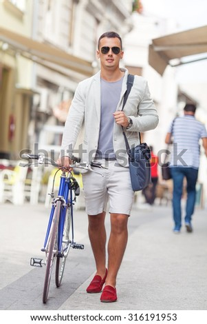 Portrait of attractive young man walking down the street with his bicycle beside him - stock photo