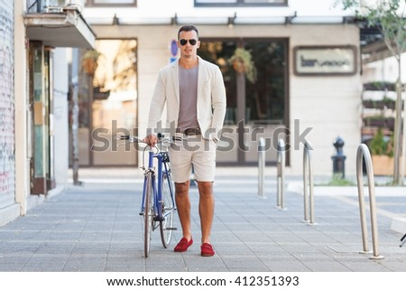 Portrait of attractive young man with his bicycle beside him. - stock photo