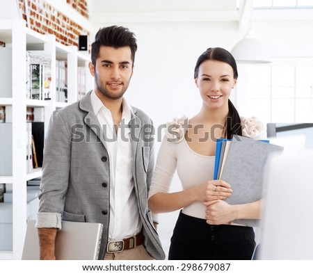 Portrait of attractive young smiling businesspeople, looking at camera. - stock photo