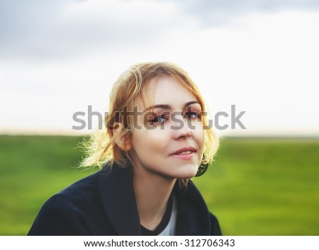 Portrait of attractive young woman in stylish clothes posing against countryside background in summer at sunset looking into camera with melancholy expression - stock photo