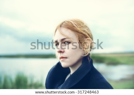 Portrait of attractive young woman on countryside with a sad expression. Frustration and stress concept. (soft-focus, vintage effect) - stock photo