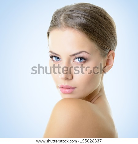 Portrait of attractive young woman over blue background - stock photo