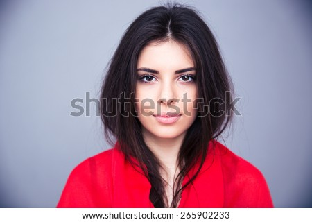 Portrait of attractive young woman over gray background. looking at camera - stock photo