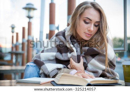 Portrait of attractive young woman reading book in cafe  - stock photo
