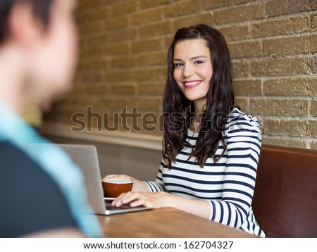 Portrait of attractive young woman sitting with laptop at table in coffee shop - stock photo