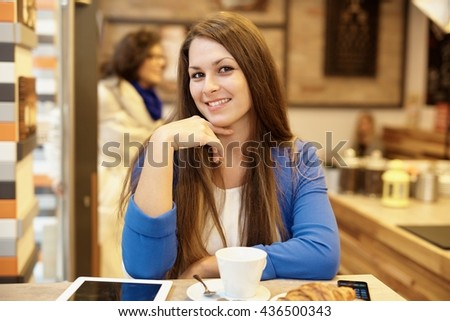Portrait of attractive young woman smiling happy in cafeteria. - stock photo