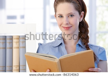Portrait of attractive young woman standing in living room at home, reading a book, smiling.? - stock photo