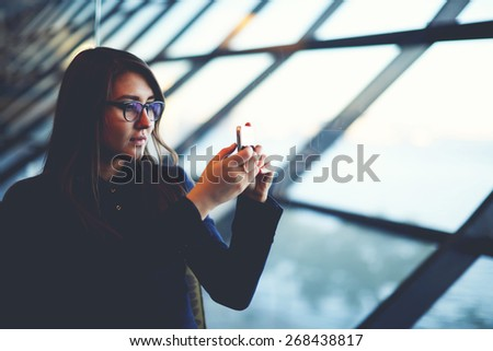 Portrait of attractive young woman taking photo with mobile cell phone sitting near big window of airport hall - stock photo