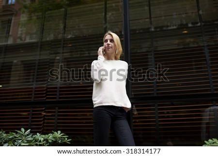 Portrait of attractive young woman talk on mobile phone while standing in the city on black empty copy space background for your text message or information, female trendy hipster at cell conversation - stock photo