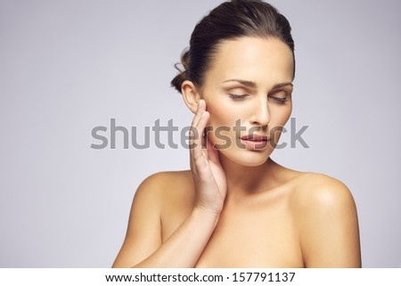 Portrait of attractive young woman touching smooth and healthy skin of her face and looking away against gray background - stock photo
