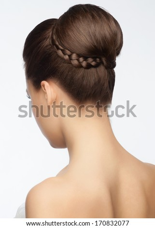 Portrait of attractive young woman with beautiful bridal updo hairstyle with tress, rear view - stock photo