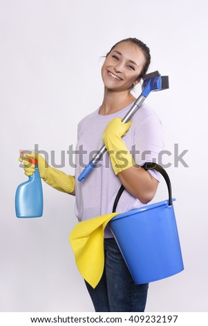 Portrait of attractive young woman with cleaning products, protective gloves and bucket. Isolated white background. - stock photo