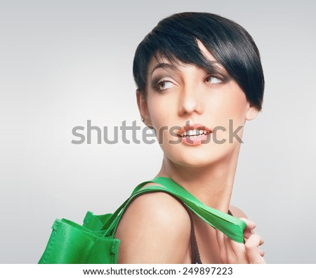 Portrait of attractive young woman with green shopping bag    - stock photo