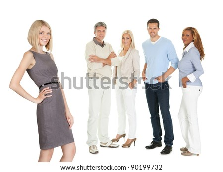 Portrait of attractive young woman with her colleagues standing at back on white - stock photo