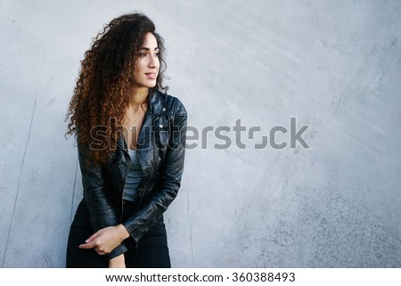 portrait of attractive young woman with long curly hair wearing a black leather jacket posing on a background of gray concrete wall with copy space area for your text or design - stock photo