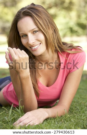 Portrait Of Attractive Young WomanLying In Park - stock photo