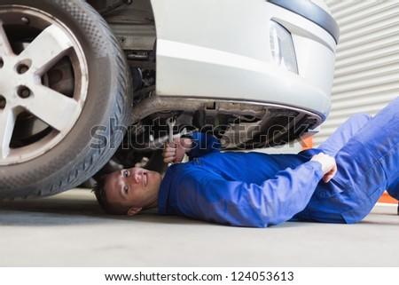 Portrait of auto mechanic under car - stock photo