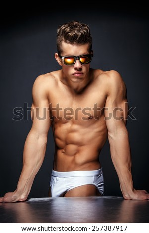 Portrait of awesome male model with naked muscular body. Isolated on dark grey background. - stock photo