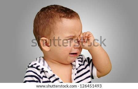 Portrait Of Baby Boy Crying against a grey background - stock photo