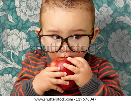 Portrait Of Baby Boy Eating Red Apple against a vintage background - stock photo