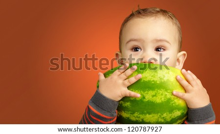 Portrait Of Baby Boy Eating Watermelon against an orange background - stock photo