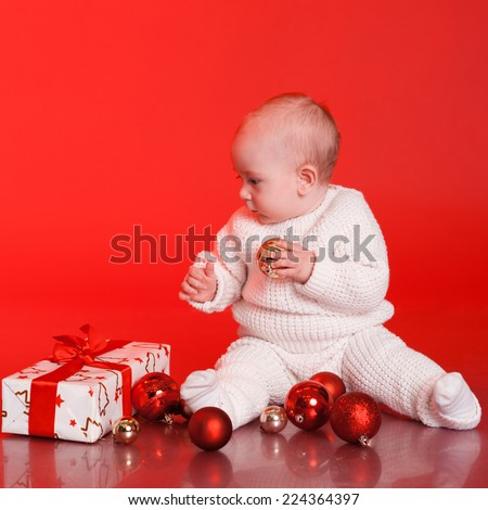 Portrait of baby boy playing with christmas decorations. Wearing knitted winter clothes over red - stock photo