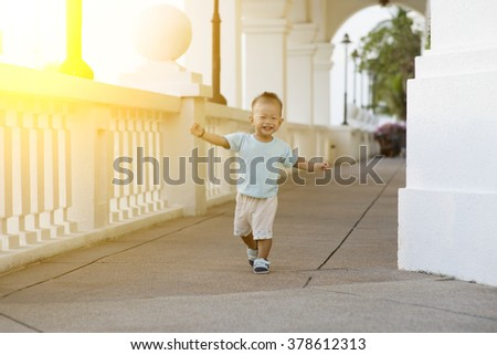 Portrait of baby boy running and smiling outdoor in sunset. - stock photo