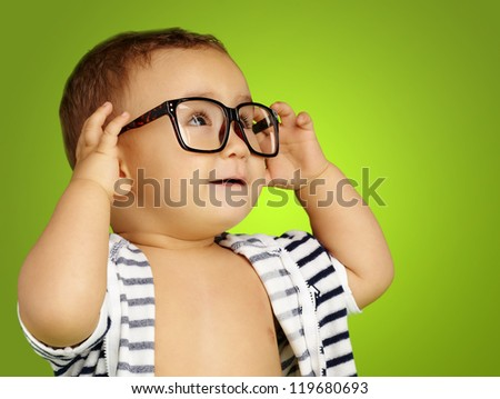 Portrait Of Baby Boy Wearing Eyeglasses against a green background - stock photo