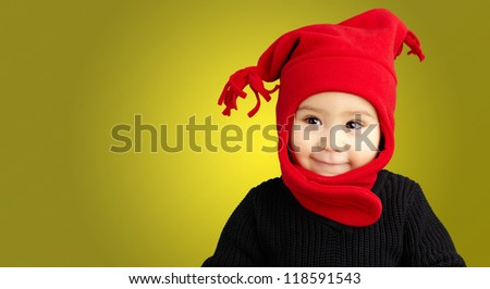 Portrait Of Baby Boy Wearing Warm Clothing against a yellow background - stock photo
