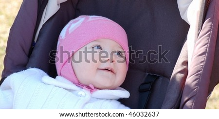 Portrait of baby girl in carriage - stock photo