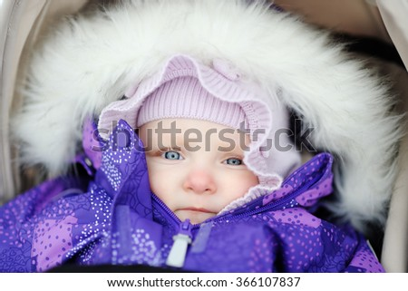 Portrait of baby girl in stroller outdoors  - stock photo