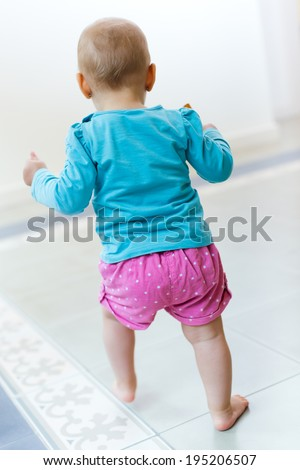 Portrait of Baby girl learning to walk at home - stock photo