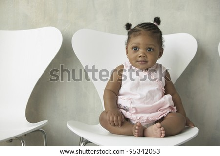 Portrait of baby girl sitting in chair - stock photo