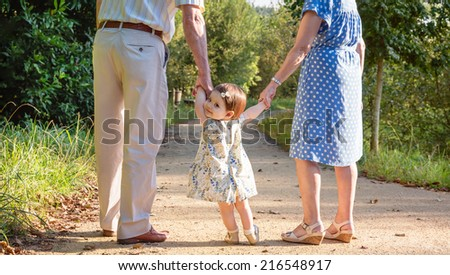 Portrait of baby granddaughter walking with her grandparents on a nature path - stock photo