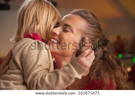 Portrait of baby hugging mother in christmas decorated kitchen - stock photo