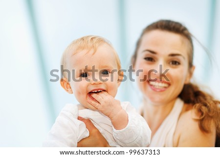 Portrait of baby playing with mother - stock photo