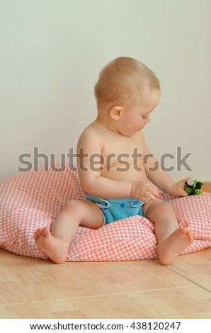 Portrait of baby wearing blue cloth nappy. Happy toddler is sitting on a big pillow and playing with locomotive. Isolated. Child concept. - stock photo
