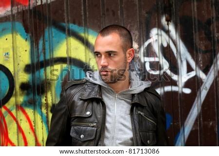 Portrait of bad boy in suburb street - stock photo
