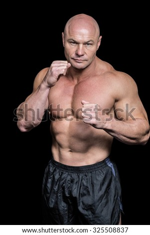Portrait of bald man with boxing pose against black background - stock photo