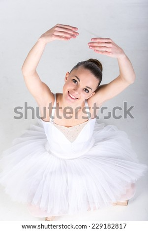 Portrait of ballerina in classical tutu in the grey studio is looking at the camera. - stock photo