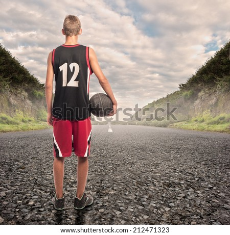 portrait of basketball player standing on a road - stock photo