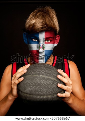 portrait of basketball player with Dominican Republic flag painted on his face - stock photo